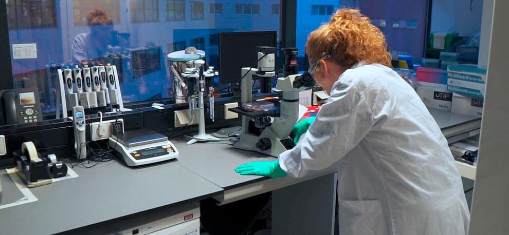 científica mirando por microscopio